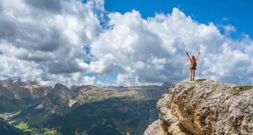 Bergsteigerin auf dem Gipfel bei strahlendem Wetter